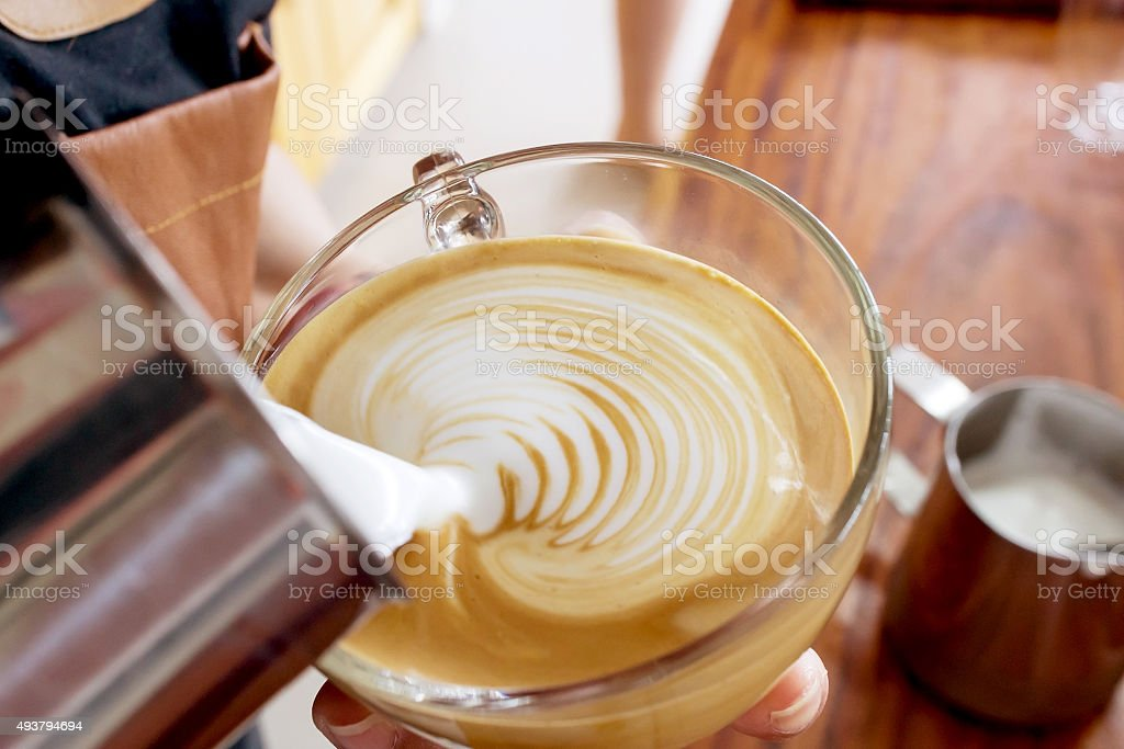 Barista making latte art in coffee cup stock photo