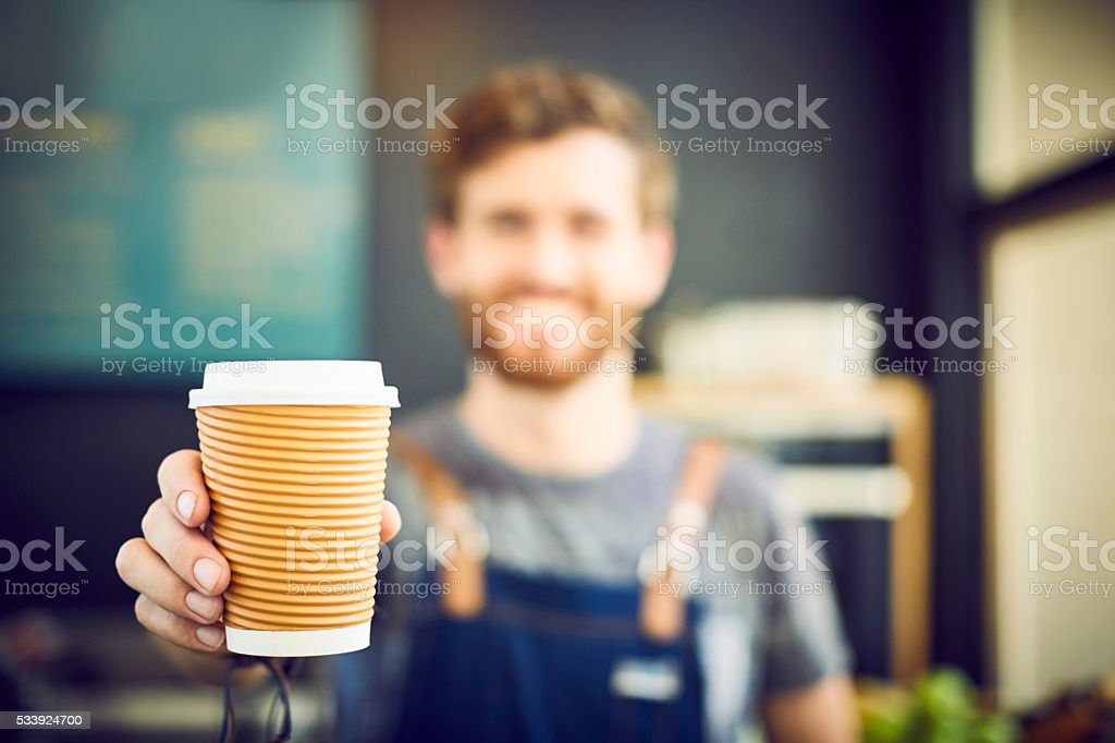 Barista offering coffee in disposable cup stock photo