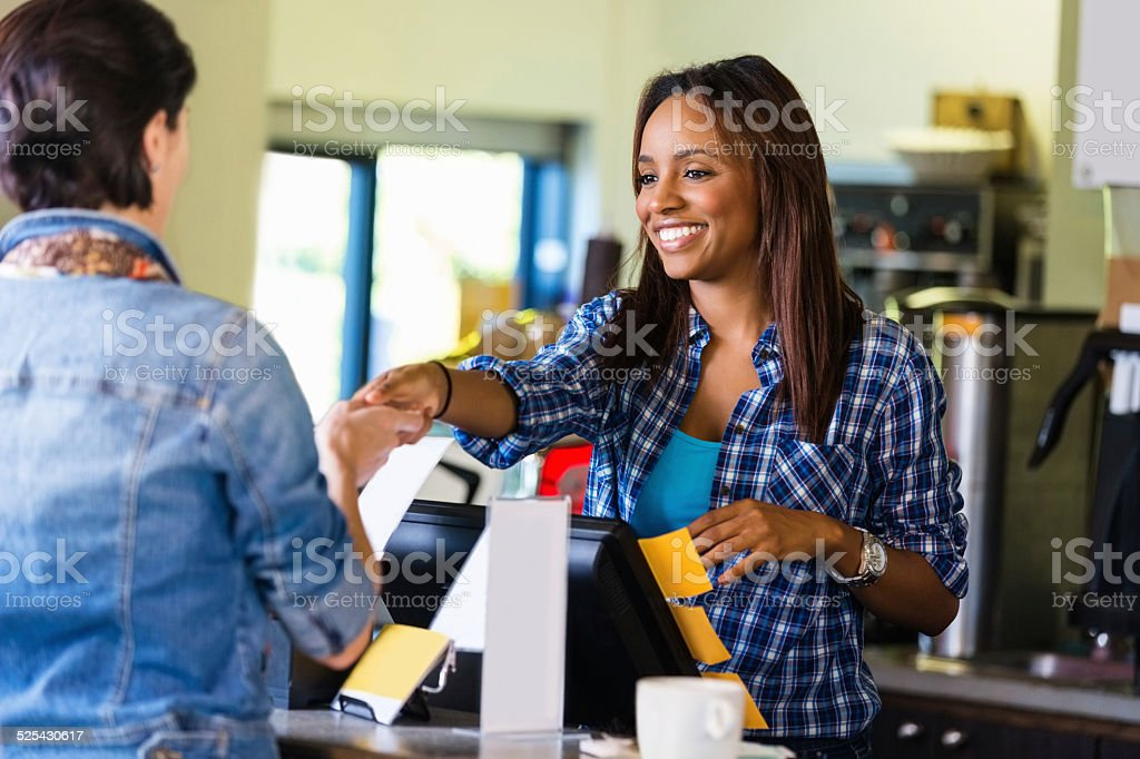 Barista or cashier accepting payment from coffee shop customer stock photo