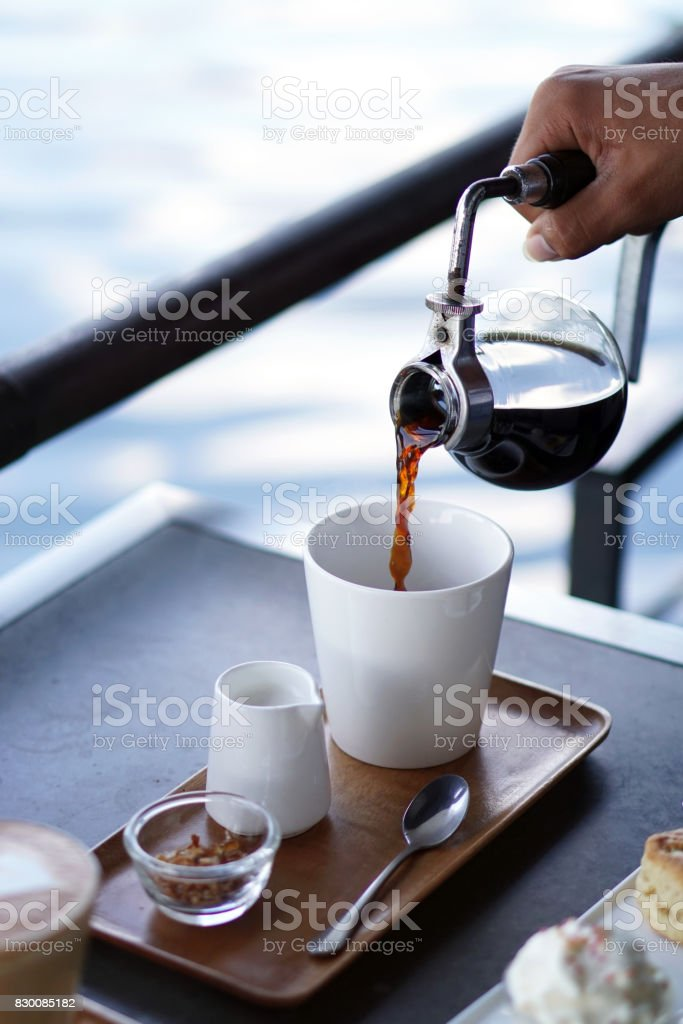 Barista pouring hot coffee from syphon coffee machine to white ceramic cup on wooden tray and blurred background. stock photo