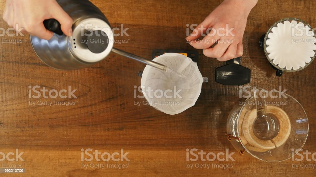 Barista pouring water on coffee ground with filter stock photo