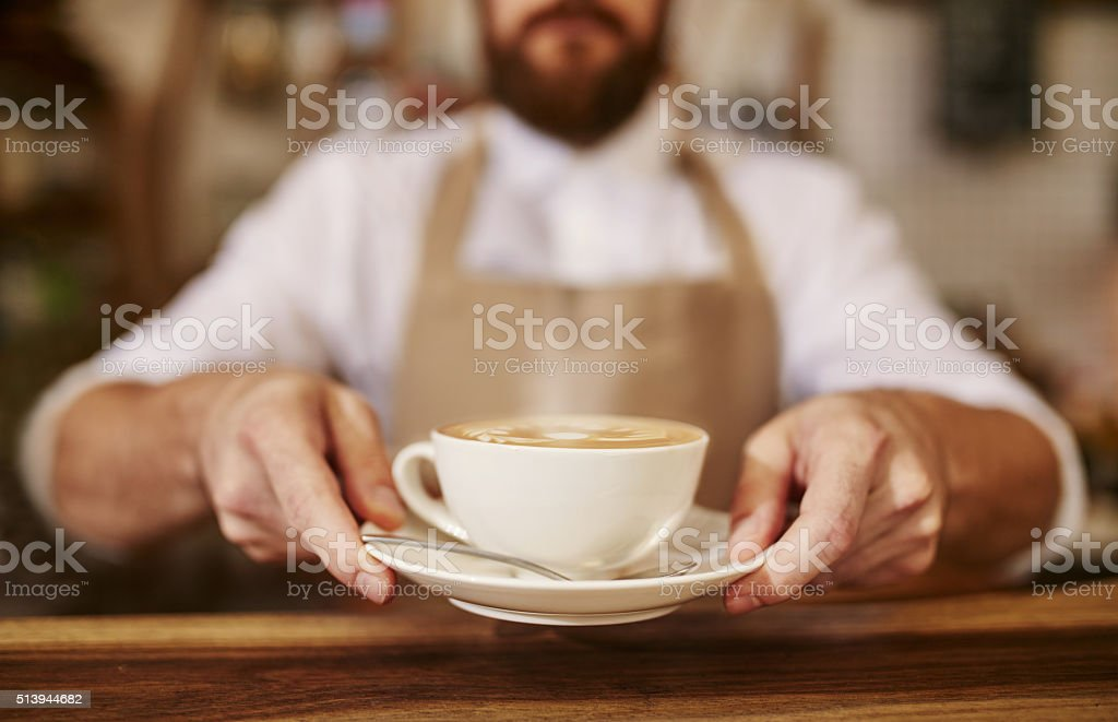 Barista serving cup of fresh coffee for you stock photo
