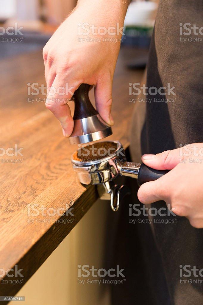Barista stamping coffe stock photo