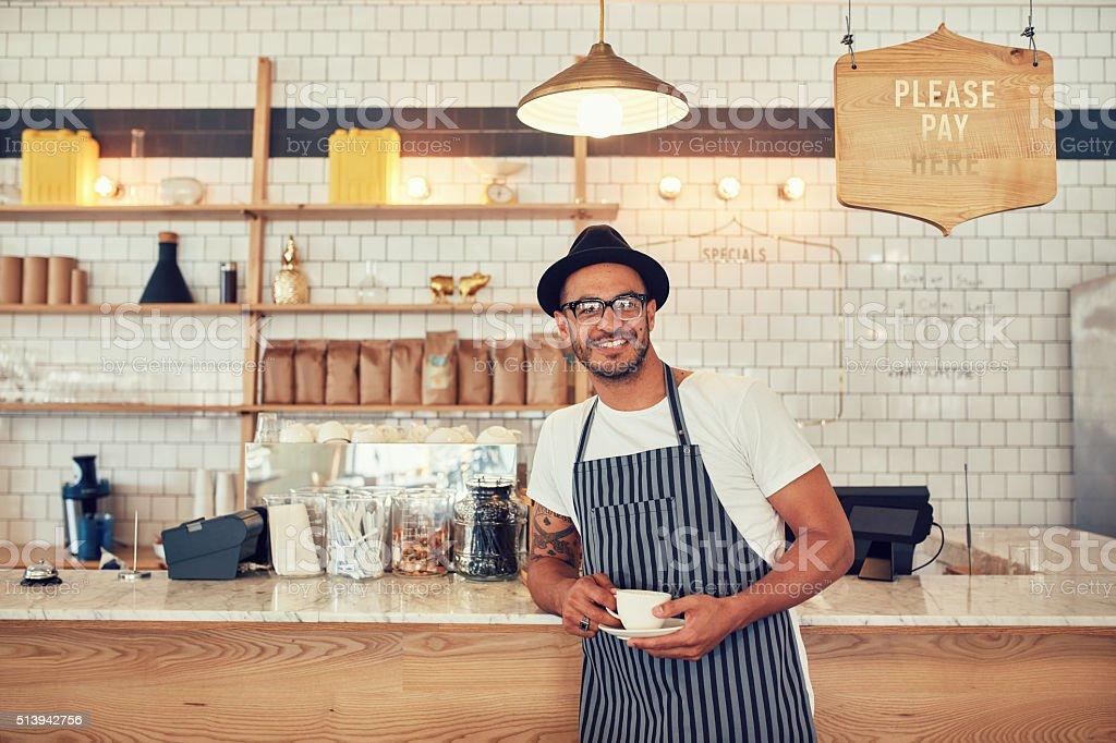 Barista standing at bar counter and smiling at camera stock photo