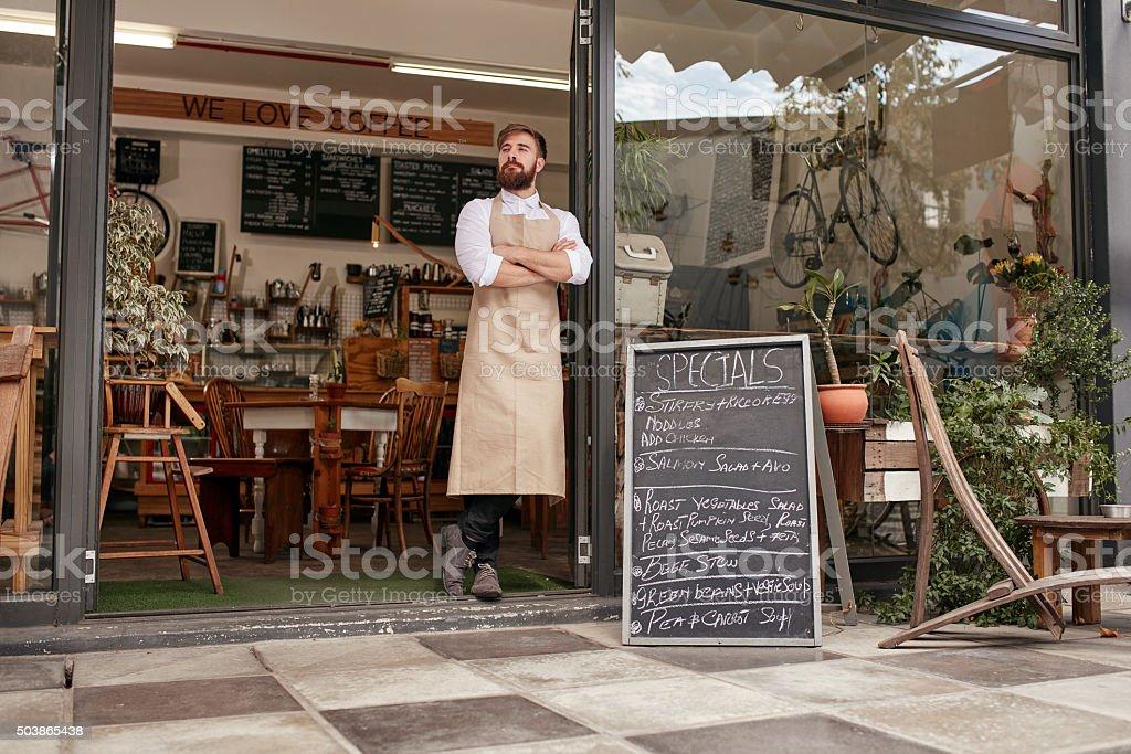 Barista standing in door of a coffee shop stock photo