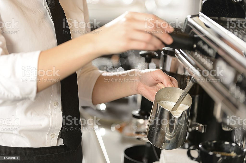 Barista steaming milk for hot cappuccino stock photo