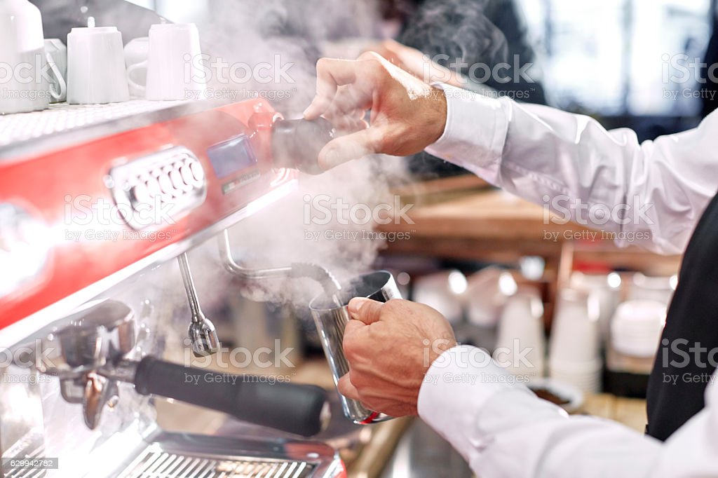 Barista steaming milk in cafe stock photo