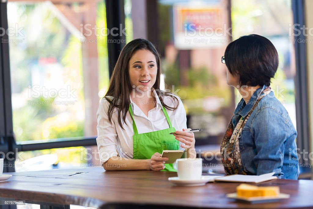 Barista taking order from customer in modern coffee shop restaurant stock photo