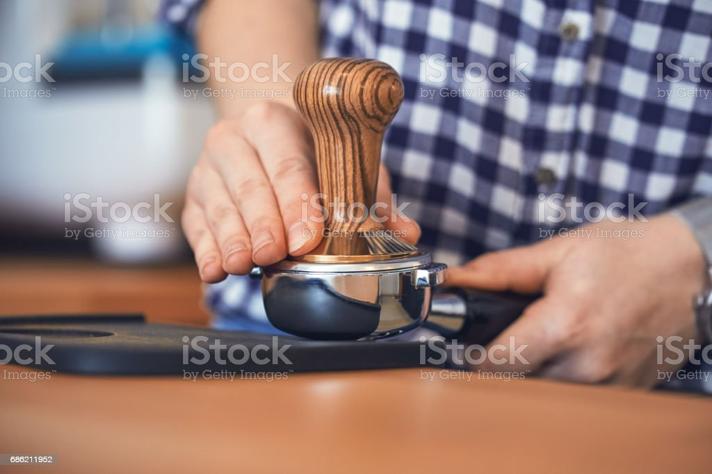 Barista tamping fresh ground coffee stock photo