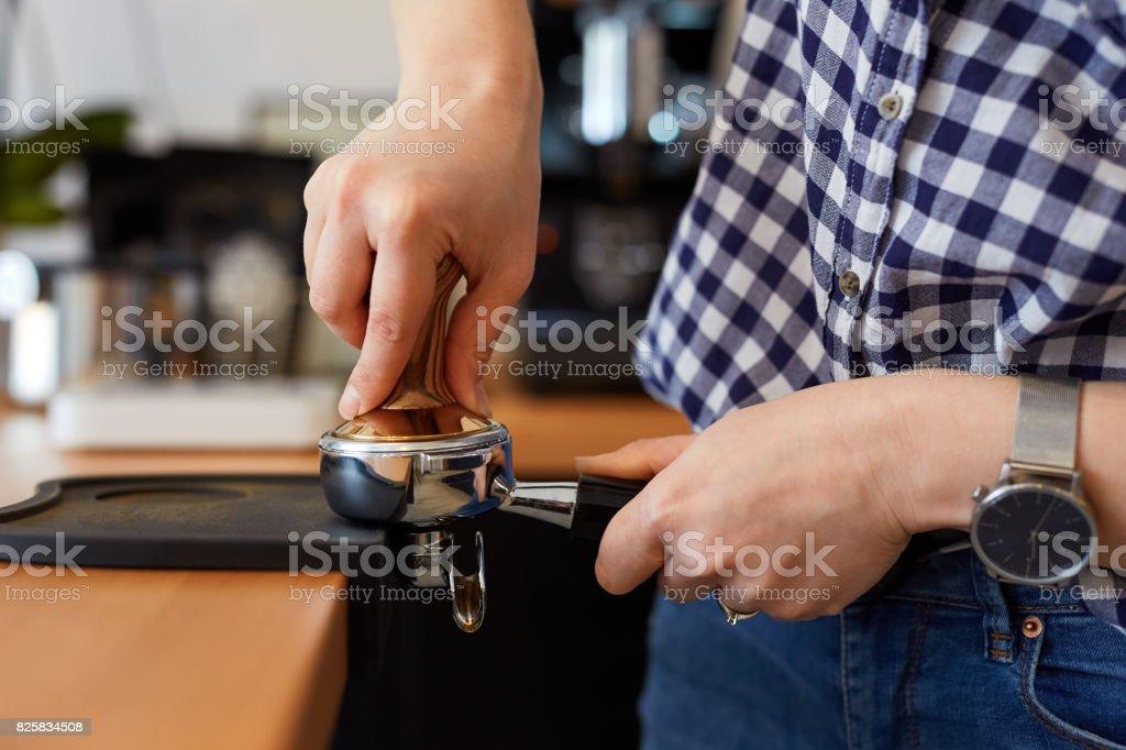 Barista tamping freshly ground coffee stock photo