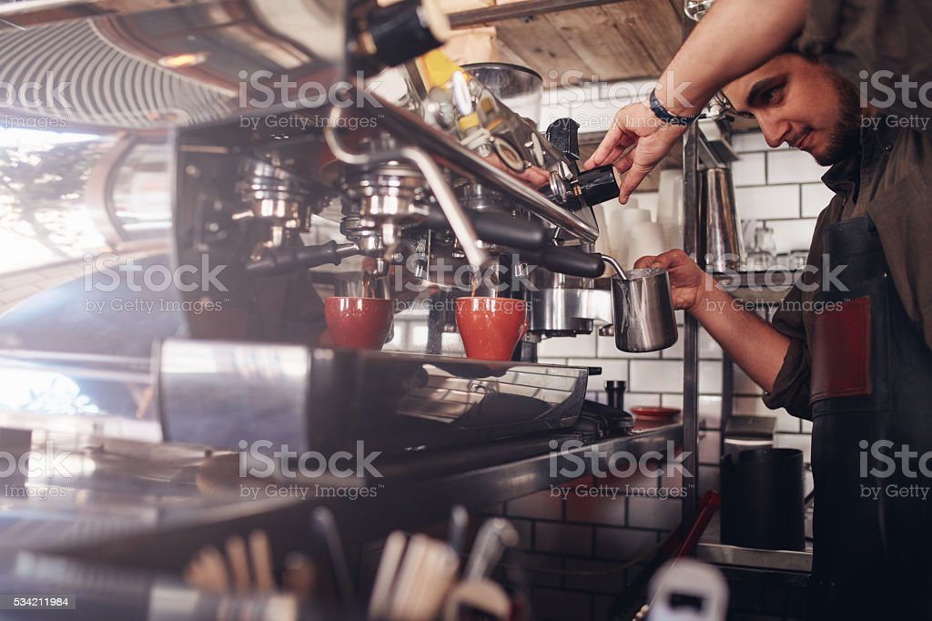 Barista using coffee maker to make a cup of coffee stock photo