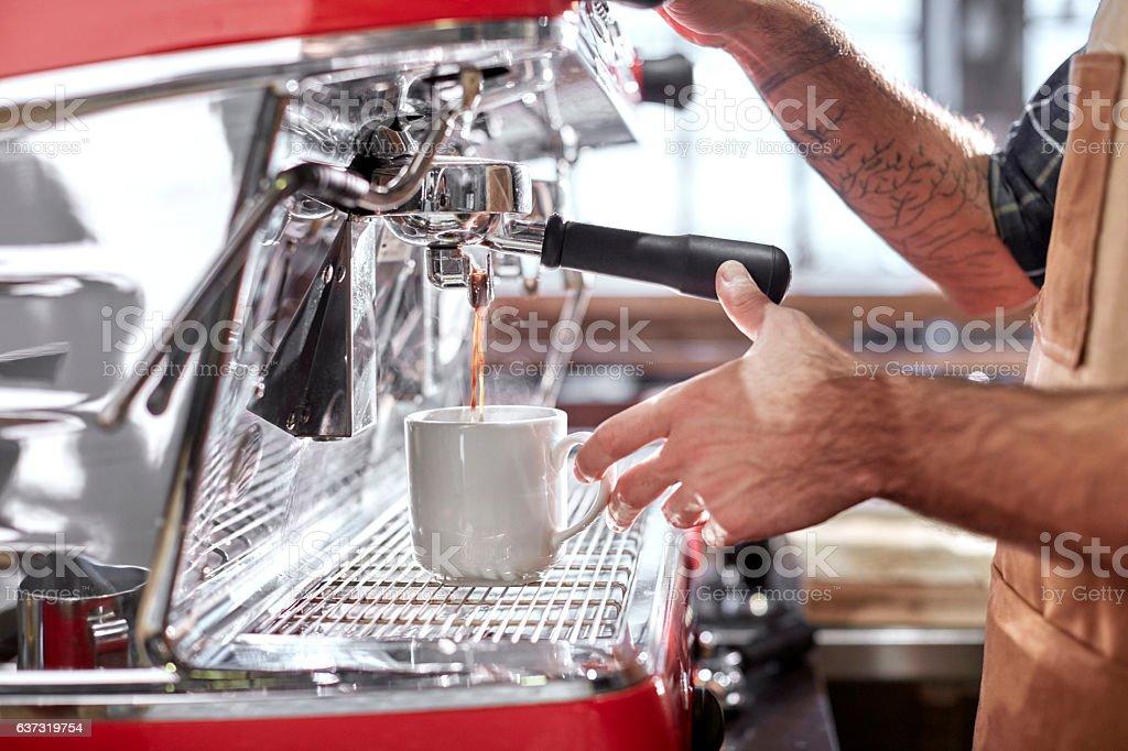 Barista using espresso machine in coffee shop stock photo