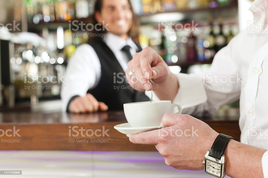 Barista with client in his cafe or coffeeshop royalty-free stock photo