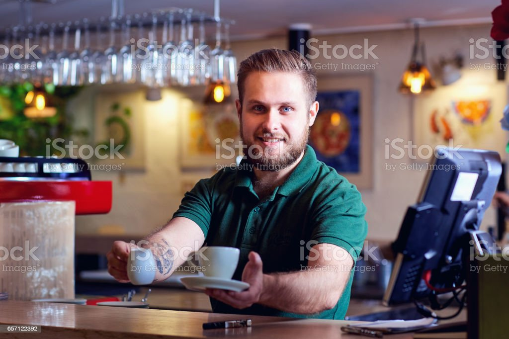 Barista with coffee cup in hand behind bar. Welcome coffee shop stock photo