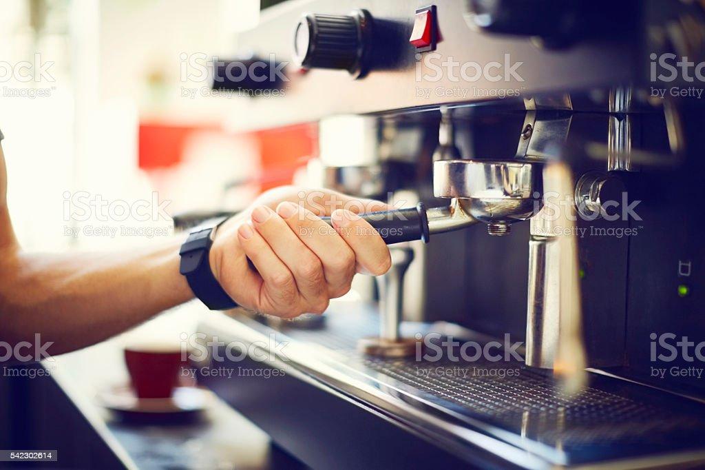 Barista's hand adjusting portafilter stock photo