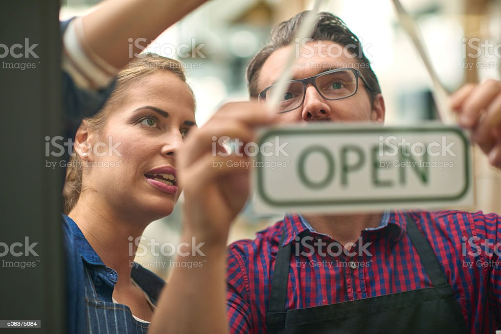 Baristas hanging up open sign together stock photo