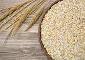 Barley flakes in wooden tray on wooden background