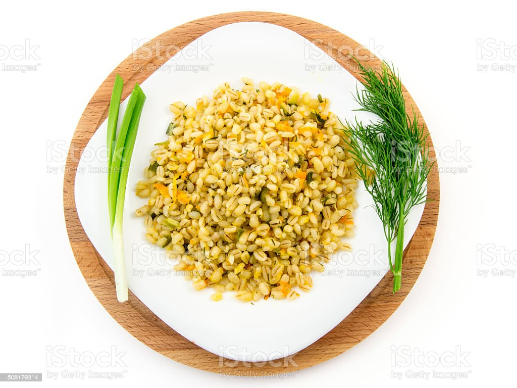 Barley porridge in plate with vegetables, dill and green onion stock photo