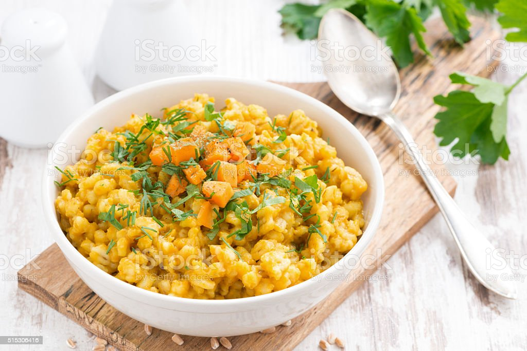 barley porridge with pumpkin and greens in a bowl stock photo