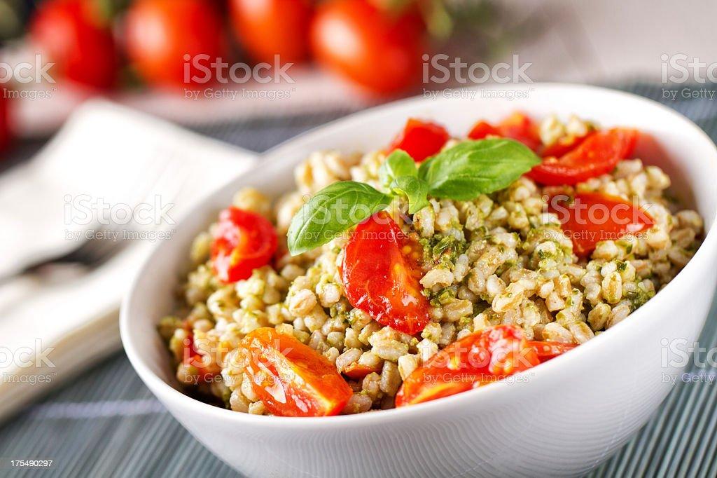 Barley with pesto sauce and tomatoes. stock photo