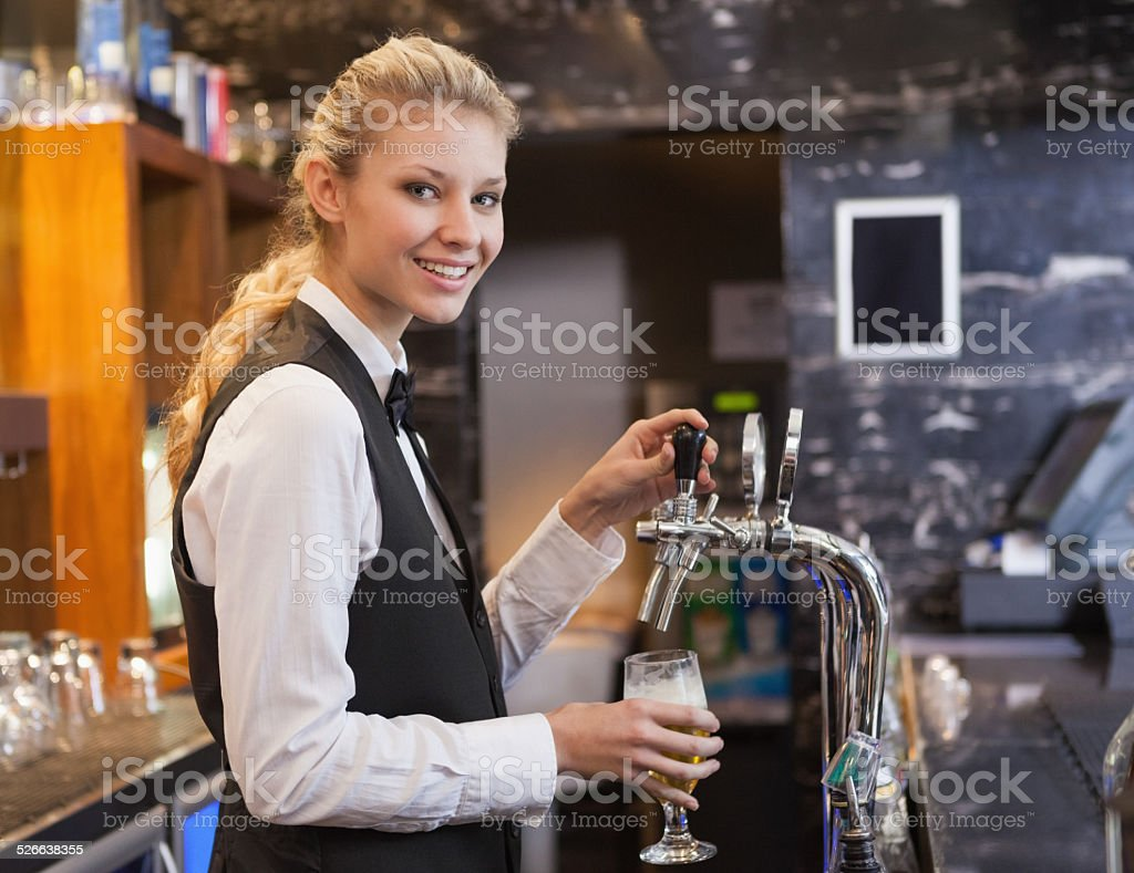Barmaid pulling a glass of beer while looking at camera stock photo