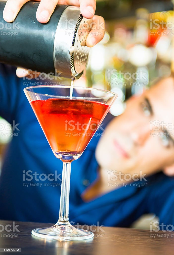Barman carefully pouring a cocktail stock photo