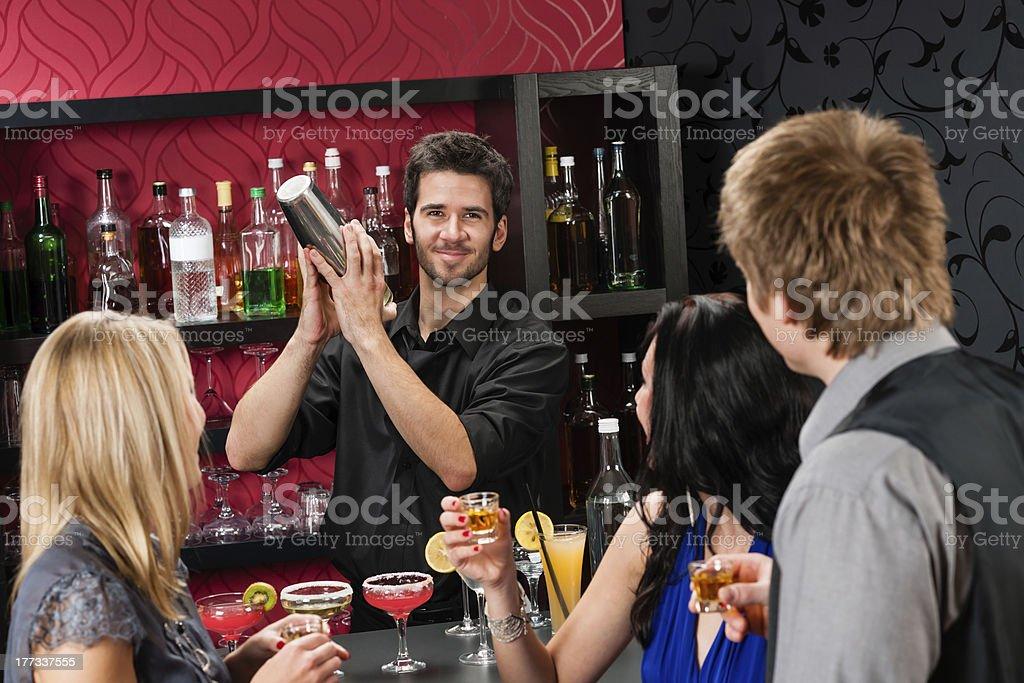Barman cocktail shaker friends drinking at bar royalty-free stock photo