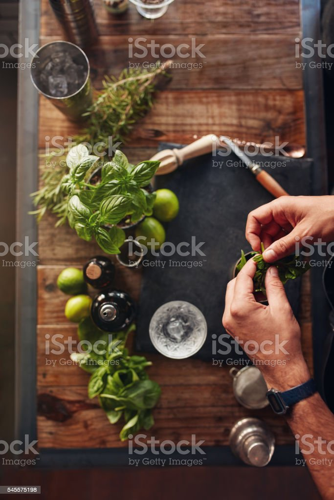 Barman experimenting with new cocktail preparation ideas stock photo