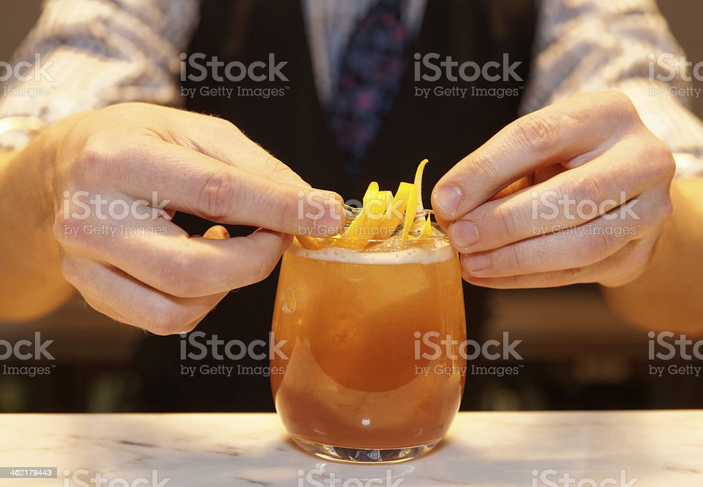 Barman is decorating a cocktail stock photo