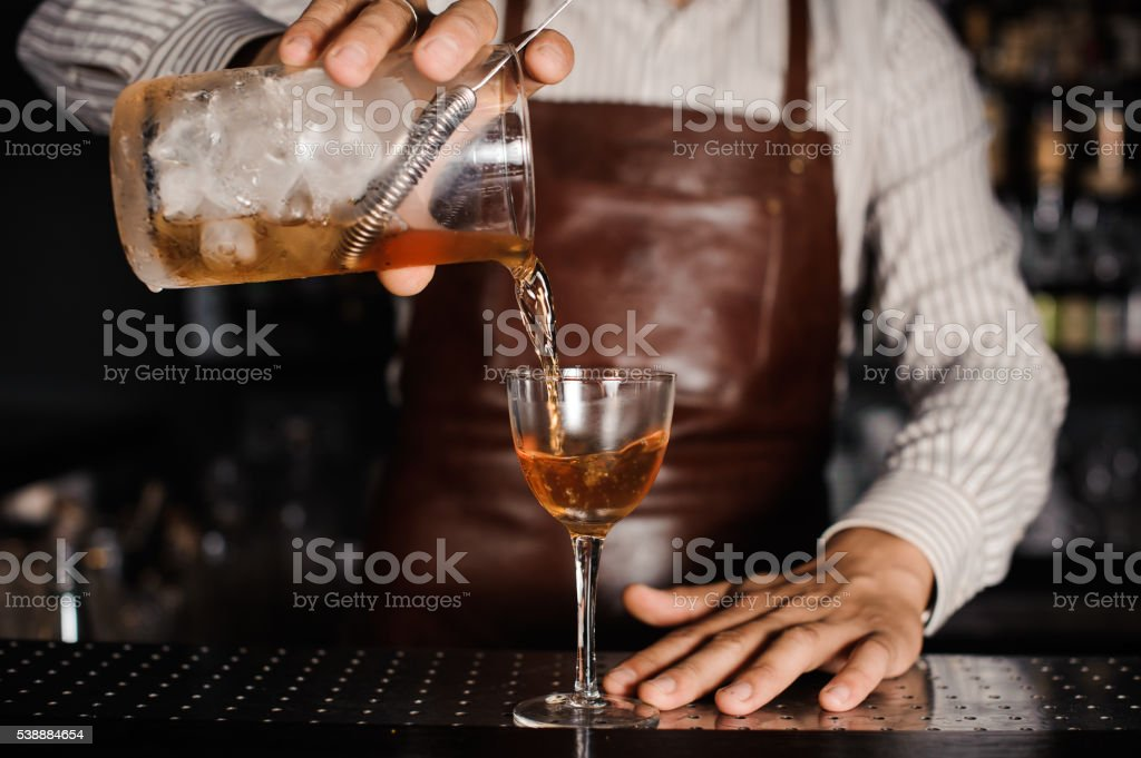 barman pouring alcoholic cocktail in glass stock photo