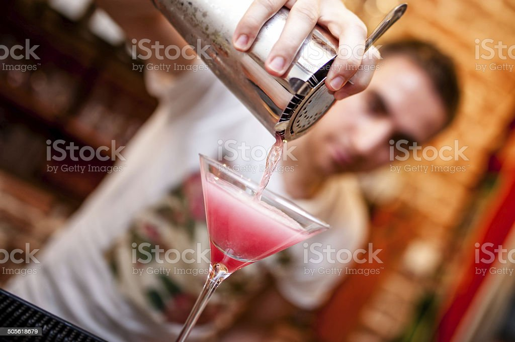 barman preparing and pouring cosmopolitan alcoholic cocktail drink stock photo