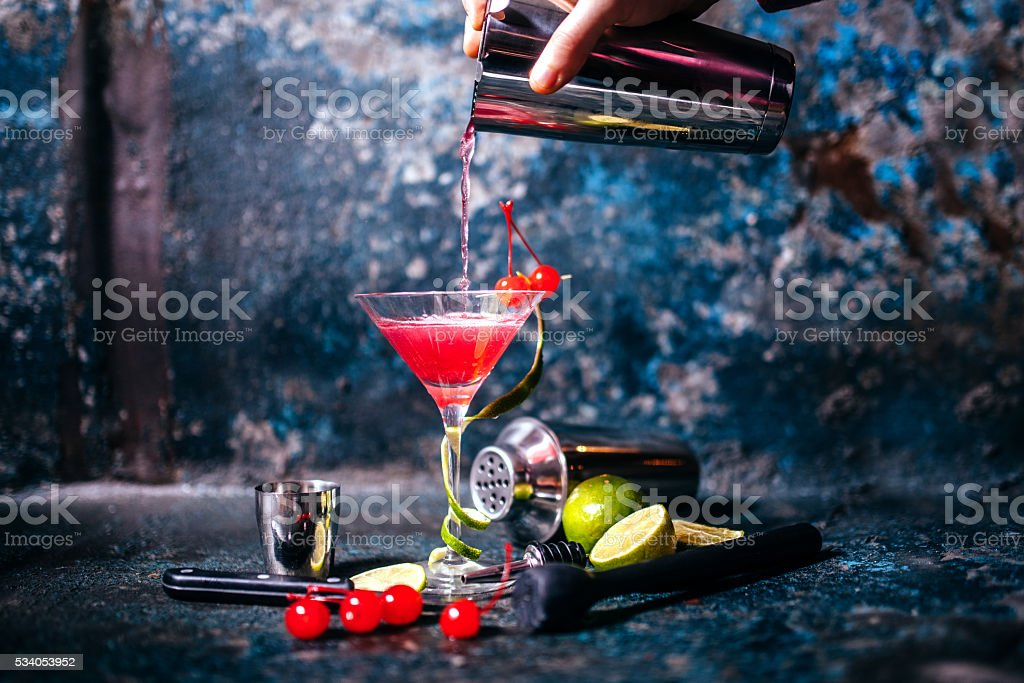 barman preparing and pouring red cocktail in martini glass stock photo