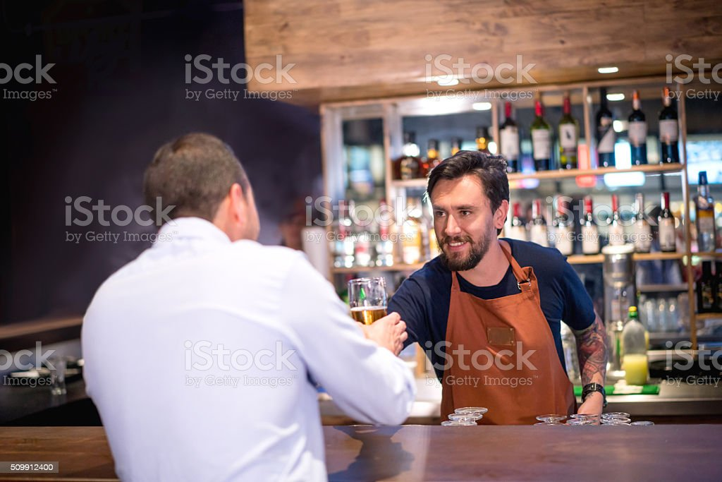 Barman serving drink to a man at the bar stock photo