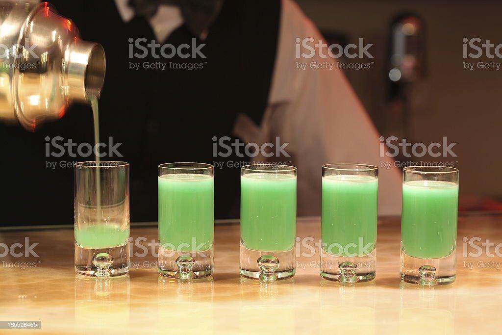 Barman serving green alcohol shots. royalty-free stock photo