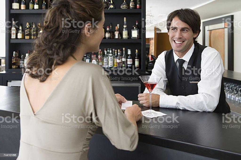 Barman serving woman stock photo