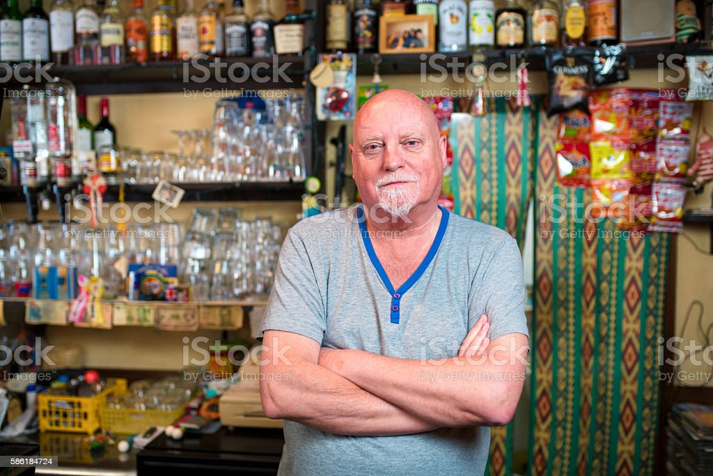 Barman stood behind the bar of his pub stock photo