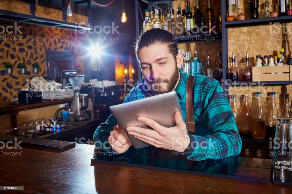 Barman with a hipster beard looks at  laptop behind  counter in the bar. stock photo