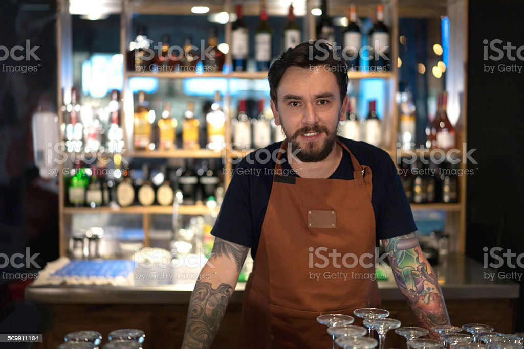 Barman working at the bar counter stock photo
