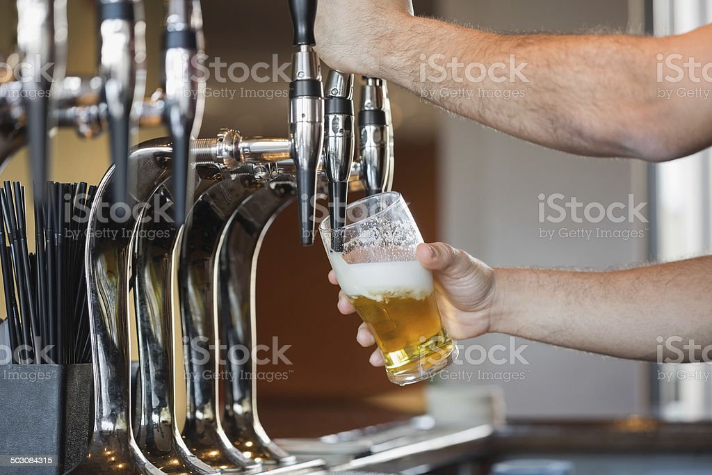 Barmans arms pulling a pint of beer stock photo