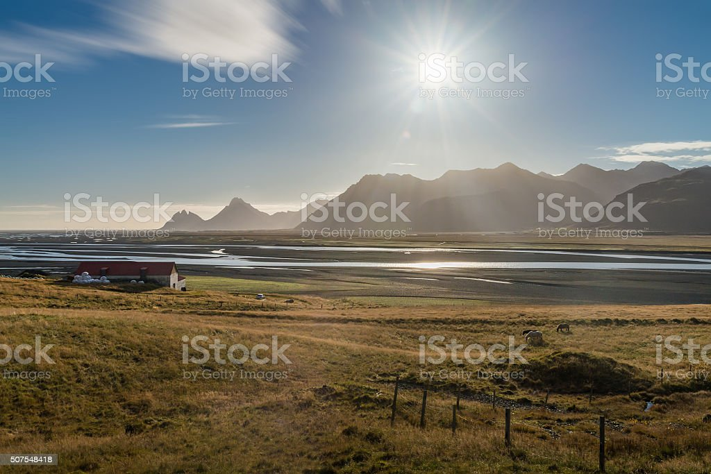 Barn farm with yellow field sea and mountain range background stock photo