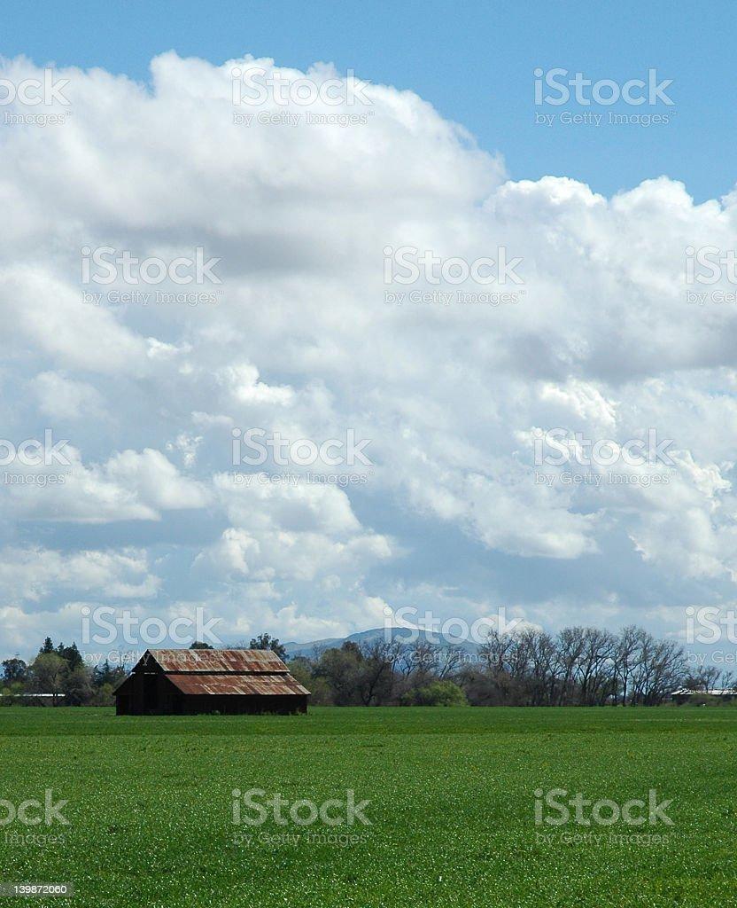 Barn in field under cloudy blue sky stock photo