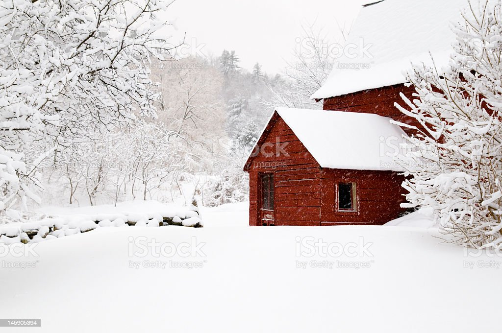 Barn in snow with stone wall and trees stock photo