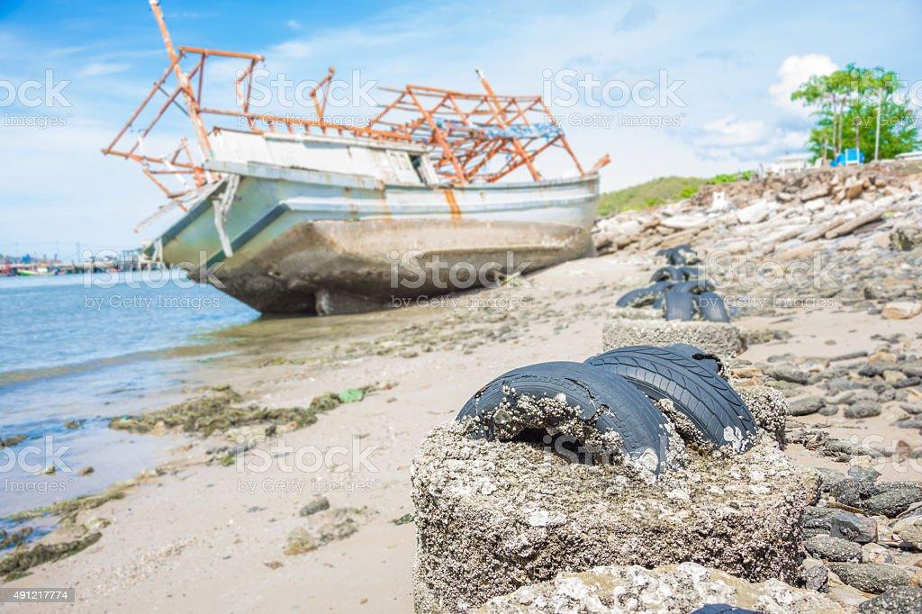 barnacle auf Reifen und Wrack Boot am Strand verwischen Hintergrund Lizenzfreies stock-foto