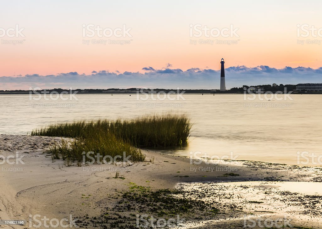 Barnegat Lighthouse at Dawn with Sand in Foreground stock photo