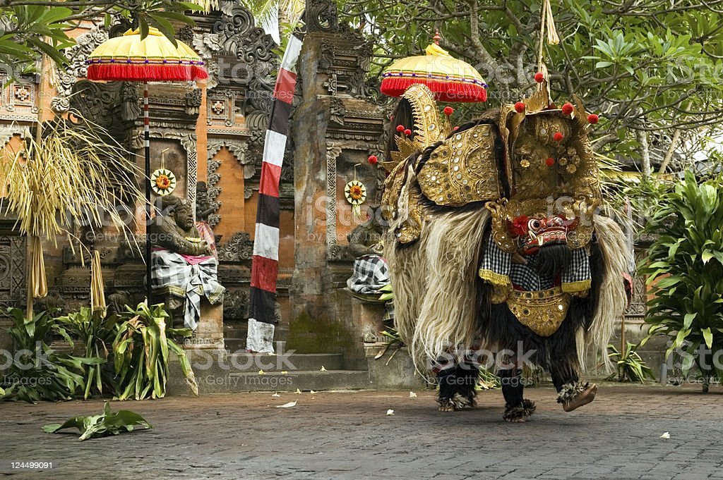 Barong dance in Bali, Indonesia next to tropical foliage stock photo