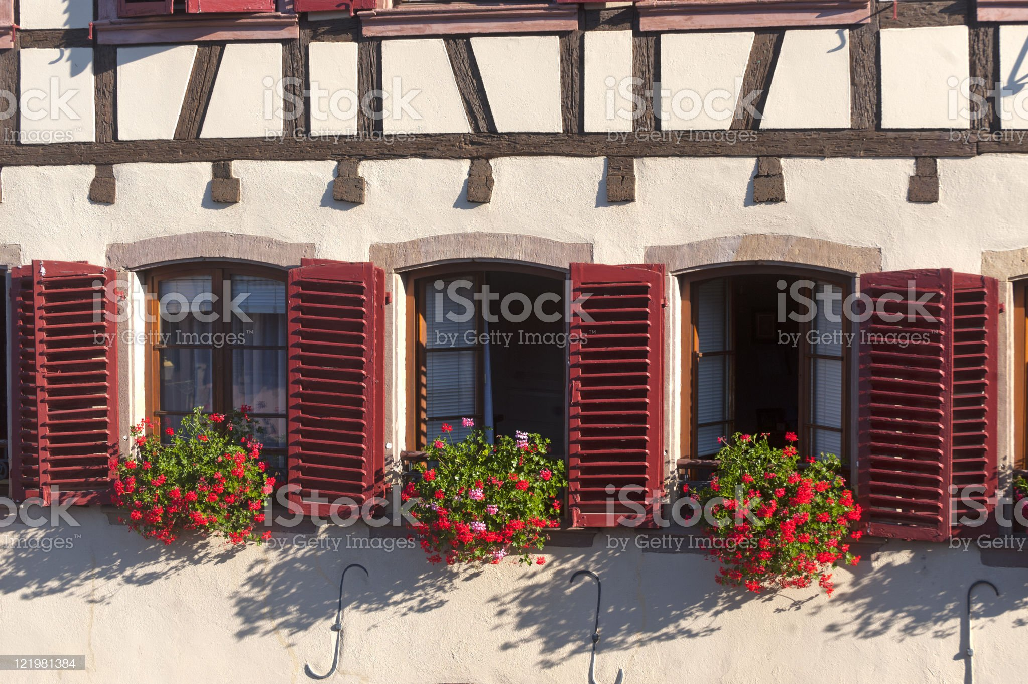 Barr (Alsace) Three windows with red shutters royalty-free stock photo