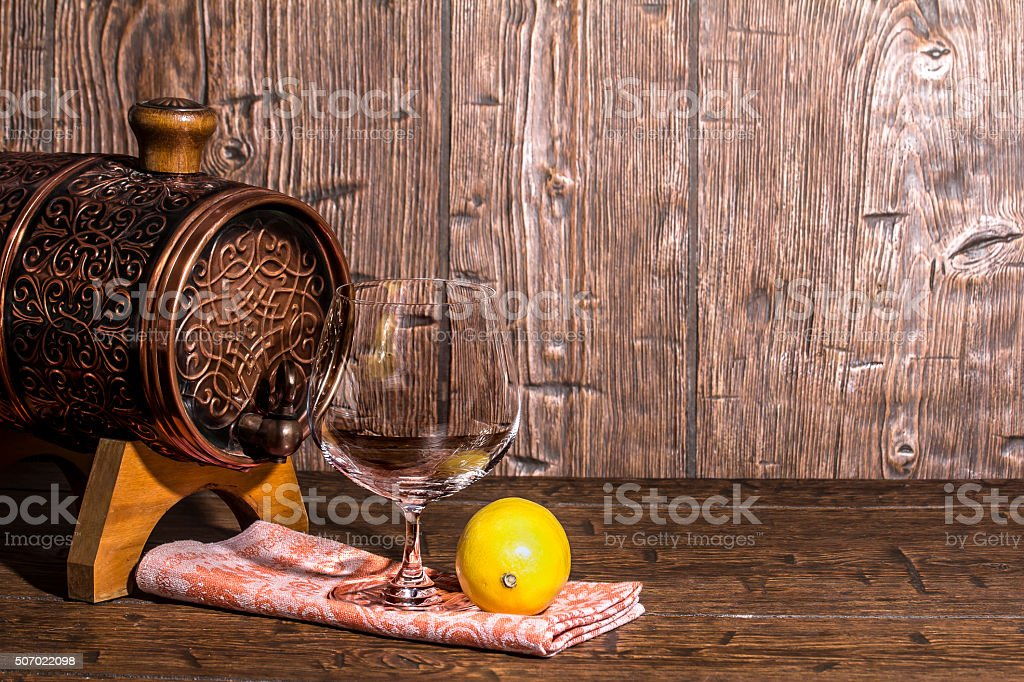 Barrel with lemon and an empty brandy glass stock photo
