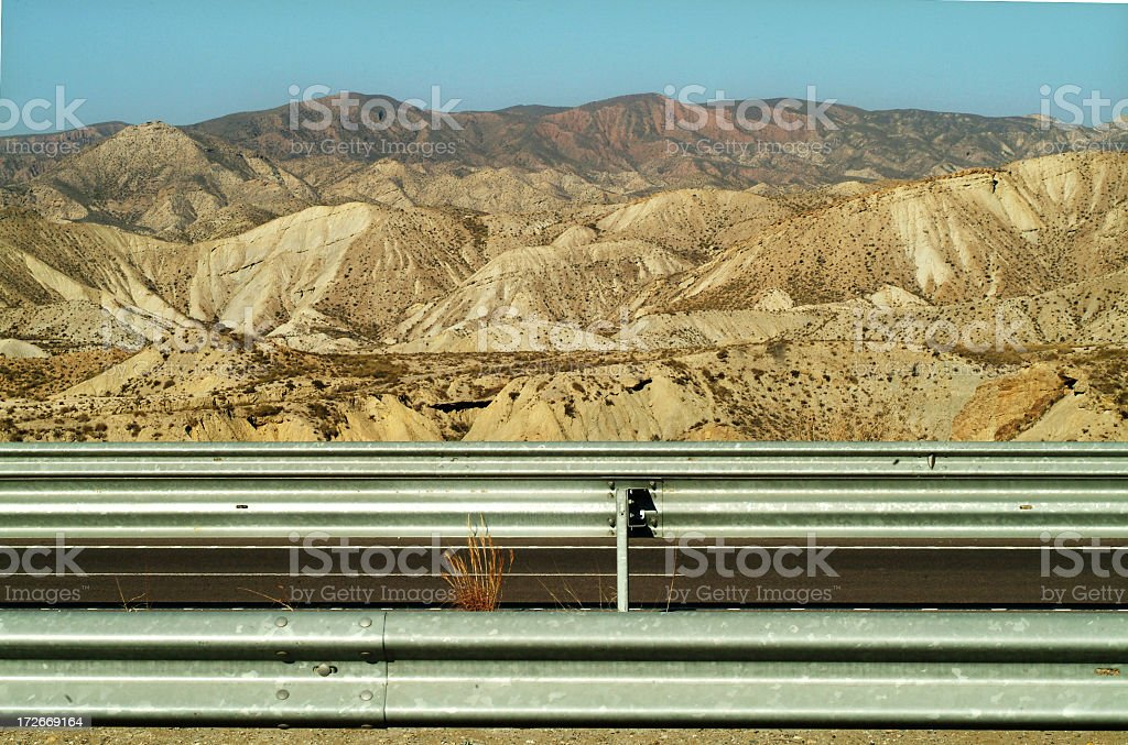 Barren hills with crash barrier desert in Spain stock photo
