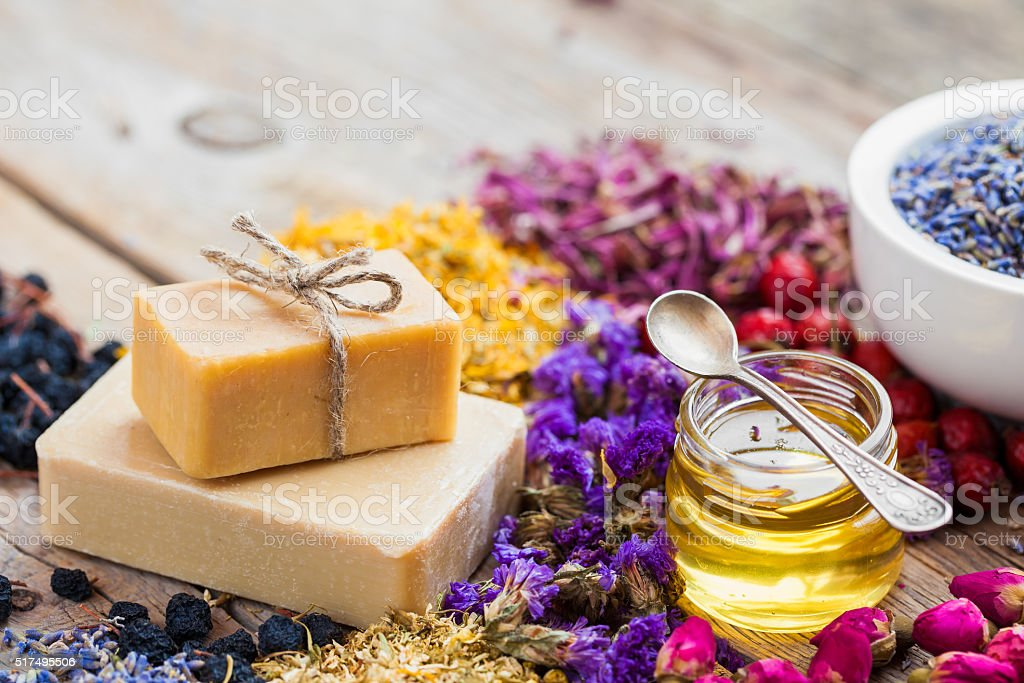 Bars of homemade soaps, honey or oil and healing herbs stock photo