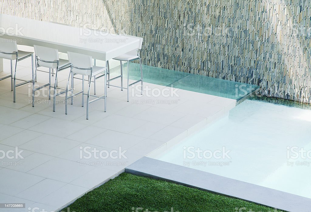 Barstools around counter on patio with swimming pool royalty-free stock photo